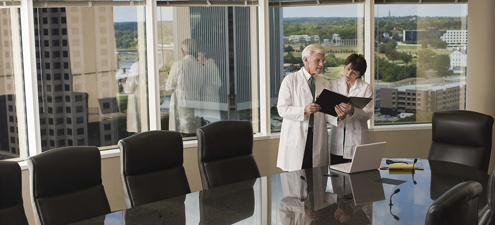 Doctors looking at folder in conference room